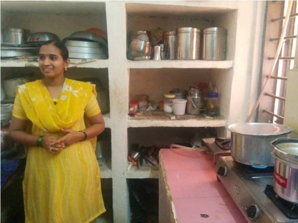 Beneficiary using biogas as a cooking fuel