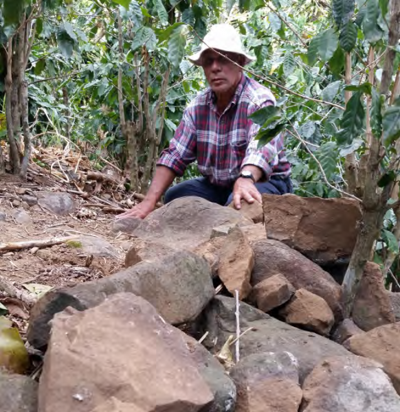 Inspecting a stone wall used to prevent soil erosion on slopes, COMDEKS Costa Rica