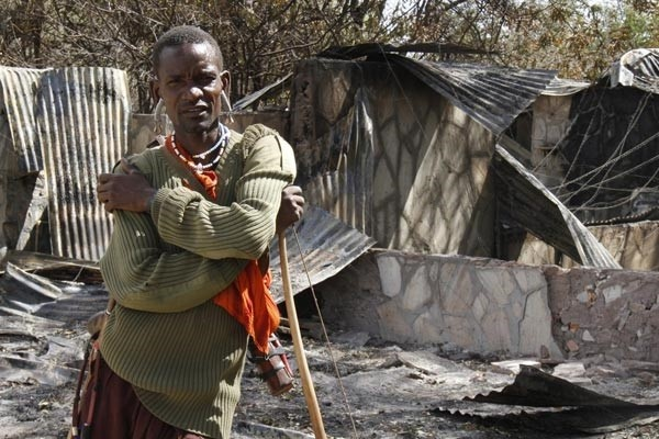 Photo 2: An armed Maasai moran guarding a burned tourist cottage at Nguruman conservancy in 2014. Photo credit: Daily Nation newspaper, November 9 2014.